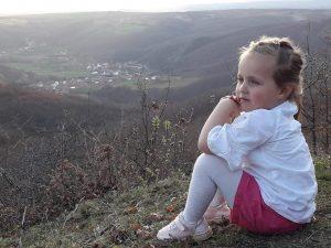 Ne ofenziven e parë te vitit 1999, akoma nuk kisha mbushë 16 vjet, pata kalu diten e parë me te gjatë te jetes time, i strukur nën shkurret e malit, qe nga mengjesi deri sa ra terri, i rrethuar nga ushtria serbe. Pa aguar dita, nje grup prej 4 vetash, u vendosëm ne mes të nje kodre me shkurre ne malet mes fshatit Rezallë dhe Tushilë, me i riu isha une, i vetmi isha qe njihja ato male, tre te tjeret ishin mysafir. Dita më e gjatë filloj, rreth ores 8 te mengjesit, pas shumë gjuajtjesh dhe bombardimeve, siper nesh 50 metra, u vendosen ushtaret serb, poashtu posht kodrës mbërriten këmbësoria serbe, ne, mbetem ne mes. Duke qene se ishim në mes te dy njesive te ushtrisë serbe, rrezikonim ne çdo moment te zbuloheshim nga këmbësoria, por nga gjuajtjet ne distanc ishim te mbrojtur, ngase ashtu do vriteshin ushtaret serb ne mes vete. Atë dite një orë nuk kishte 60 minuta, sensi i kohes kishte ndryshuar, e shikoja djellin, oh sa ngadal levizte, veç komunikimit me sy, mes grupit asnje fjal nuk e kemi fole. Me kujtohet sa te rrezikuar kemi qenë nga nje qen me lara, i cili vinte nga ushtarët serb qe ishin posht kodres afer perrojt ( afersisht 100 metra larg nesh), dhe na ofrohej neve deri 10 metra, na shikonte dhe lehte her pas here, por per fatin tone nuk turrej aq qe te bente me kuptu qe ka hetuar diçka. Gjithe diten e kemi kaluar ne 10 m2, veç shikimeve dhe gjesteve, asnje ze se kemi nxjerrë. Dy pjestar te grupit ishin vëllezër, tezak te mijë, nga ne gjithësej vetem 2 veta e kishin te mbaruar sherbimin ushtarak. O Zot sa stabil kemi qenë..., aty mjaftonte nje kollitje, shkarravinë, a nje veprim i pa kontrolluar dhe gjithçka do merrte fund. Pas shumë e shumë gjuajtje, filloj nje qetësi, serbet ndërruan taktiken, filluan te bëheshin sikur jan terhequr, dhe filluan te thirrnin emra shqiptar, te thonin, hajdeni sa kan shku.... Duke qenë se siper nesh kishte makineri ushtarake, tanke etj, ne e dinim se per tu terhjekur duhet behet shumë zhurmë e makinerive ushtarake, ajo nuk kisht